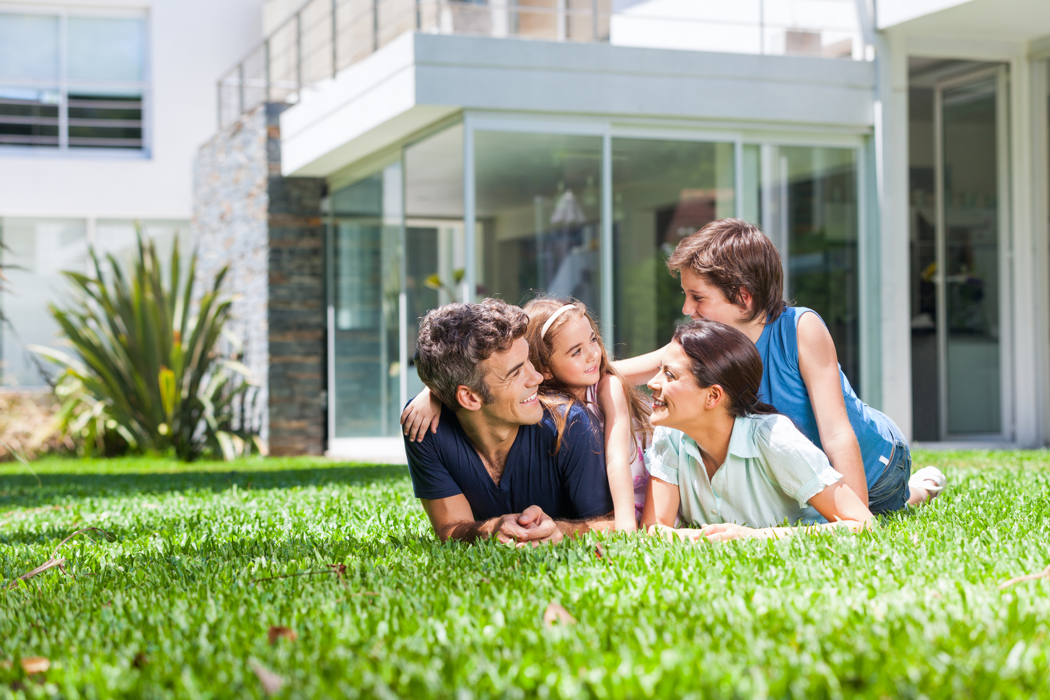 happy family lying on grass in the back of the house.