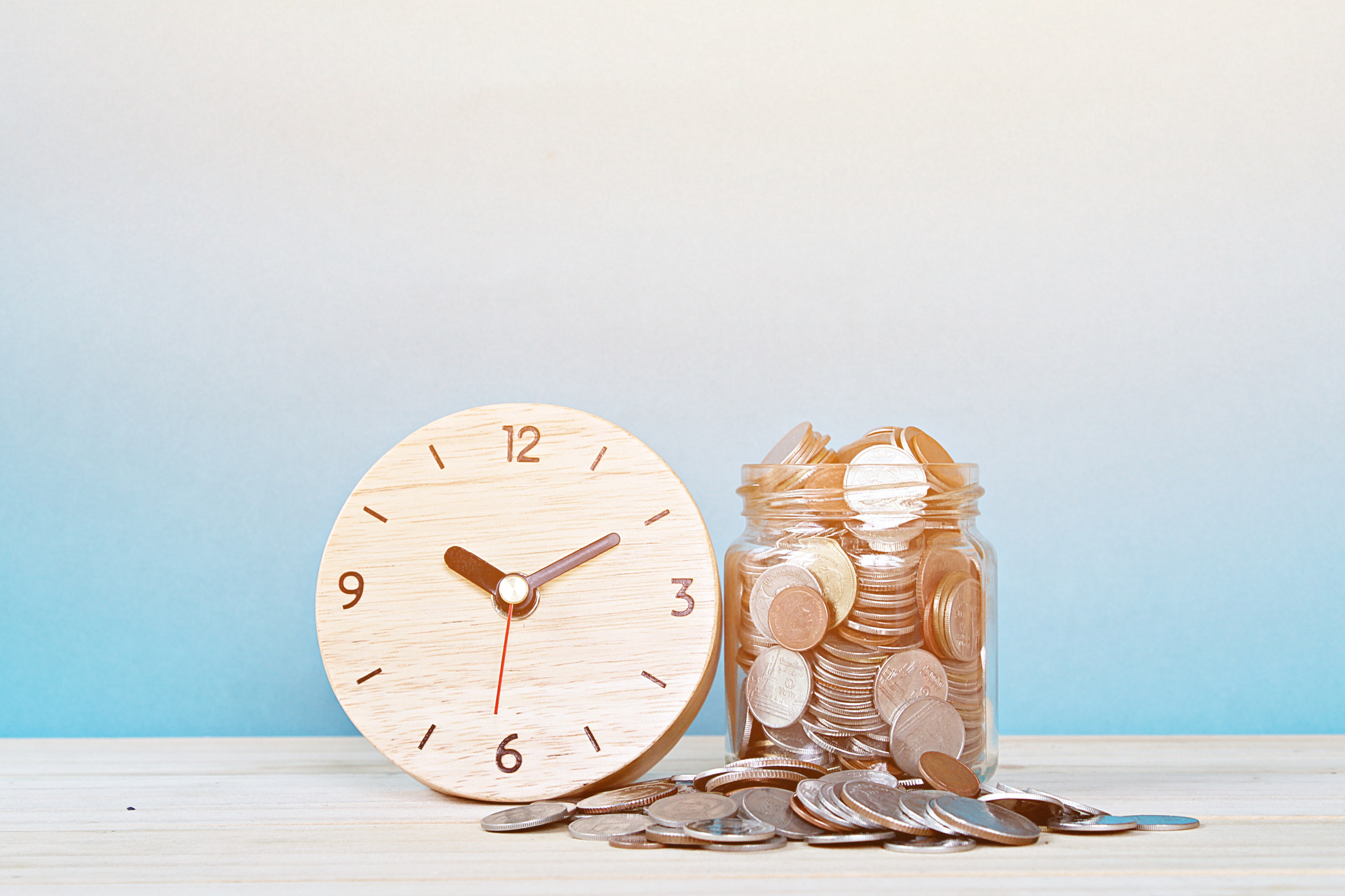 white clock next to jar of money for buy now pay later concept
